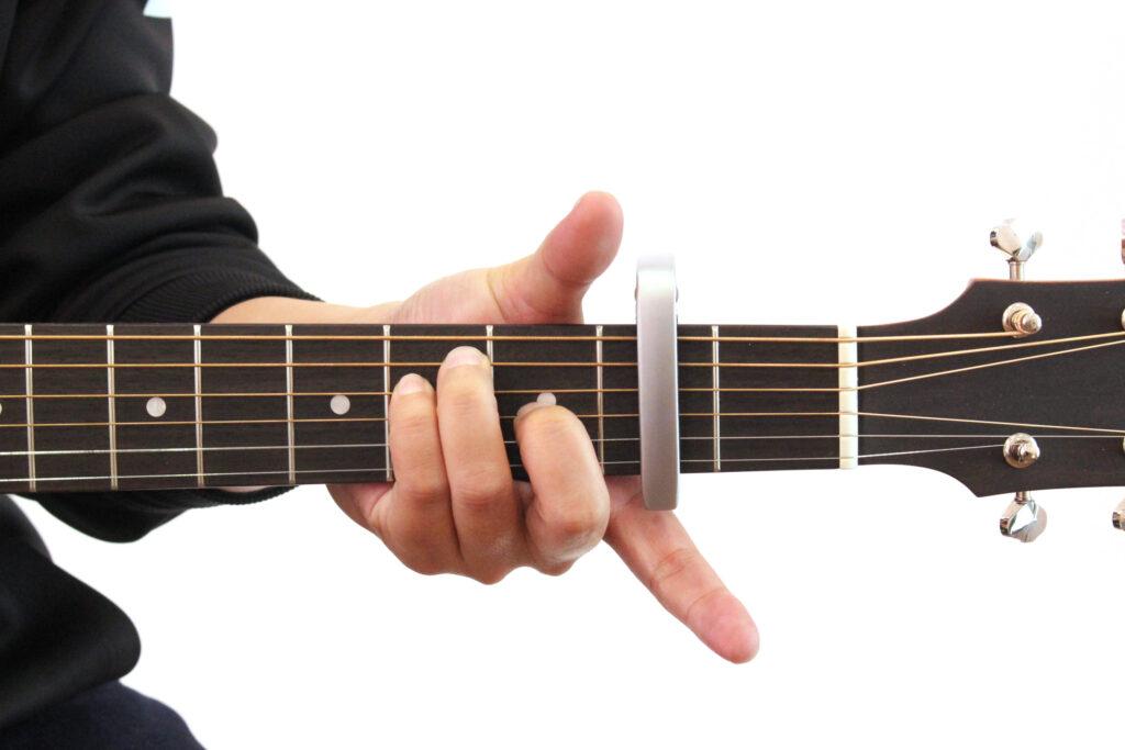 ギターカポをアコースティックギターの2フレットに装着しEのコードを押さえたところ。この場合音はG♭になる