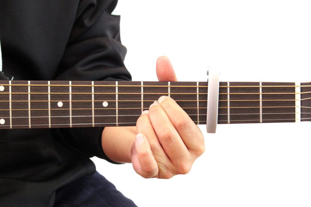 ギターカポをアコースティックギターの3フレットに装着しAのコードを押さえたところ。この場合音はCになる
