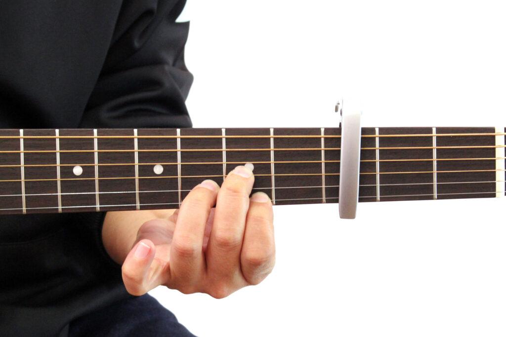 ギターカポをアコースティックギターの3フレットに装着しDのコードを押さえたところ。この場合音はFになる
